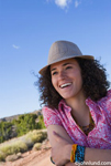 Picture of a smiling happy ethnic woman wearing fedora and a pink print blouse. Big hair.